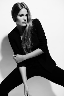 High fashion look.glamor portrait of beautiful sexy stylish caucasian young woman model in black clothes posing near wall