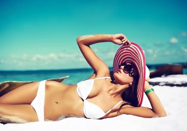 High fashion look.glamor sexy sunbathed model girl in white lingerie bikini in colorful sunhat posing behind blue beach ocean water