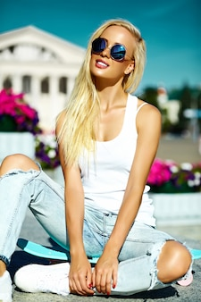 High fashion look.glamor stylish beautiful young blond  model girl teenager in summer bright casual hipster clothes with skateboard