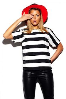 ファッション性の高い外観。グラマースタイリッシュなかわいい美しい若いブロンドの女性モデル夏の赤い明るい帽子でカラフルなヒップスター布