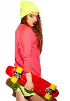 High fashion look.glamor stylish sexy beautiful young brunette woman model in summer bright hipster cloth in yellow beanie with skateboard