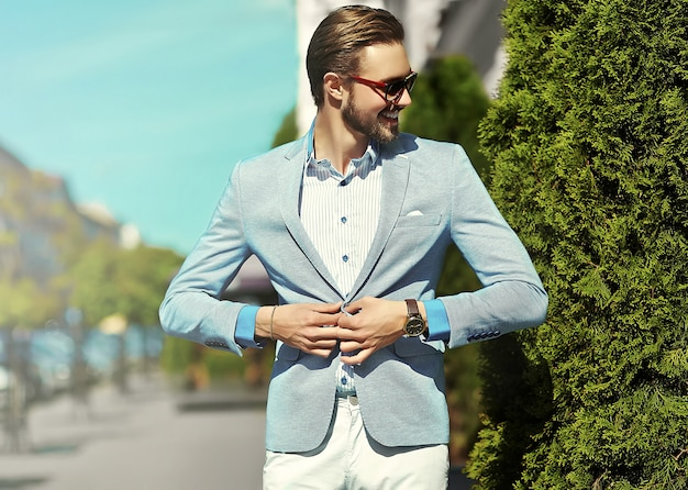 High fashion look.young stylish confident happy handsome businessman model in suit clothes lifestyle in the street in sunglasses