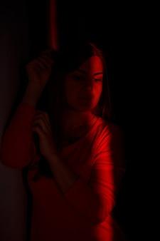 어둠 속에서 빛의 광선에 하이 패션 모델. 매력적인 섹시 한 여자 크리에이 티브 유행 초상화입니다. 여성의 얼굴에 광선의 지향성