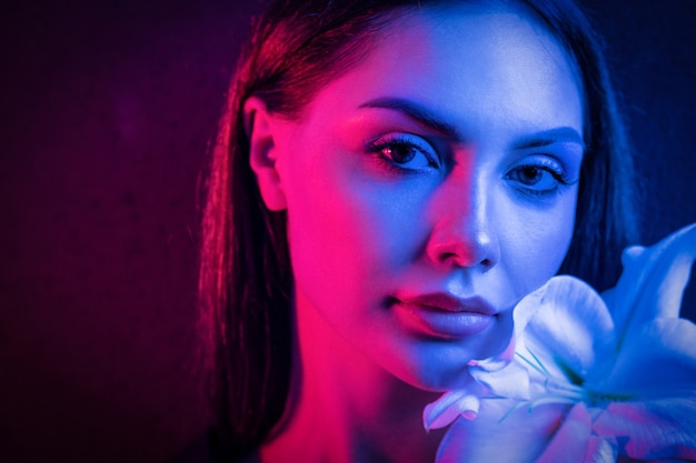 High fashion model metallic silver lips and face woman in colorful bright neon uv blue and purple lights