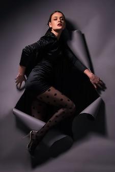 찢어진 종이를 밟는 스타킹으로 포즈를 취하는 하이 패션 모델