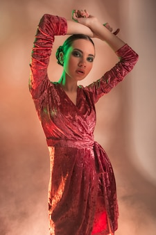 High fashion model woman in colorful bright lights posing in studio,