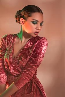 スタジオでポーズをとってカラフルな明るいライトでファッション性の高いモデルの女性