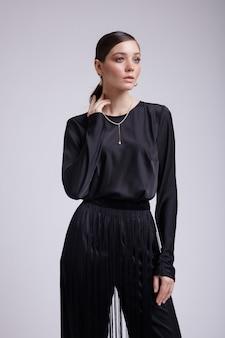 灰色の背景に黒のブラウスフリンジパンツアクセサリーでエレガントな女性のハイファッション写真