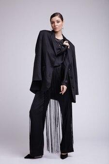 灰色の背景に黒のジャケットブラウスフリンジパンツアクセサリーの女性のハイファッション写真