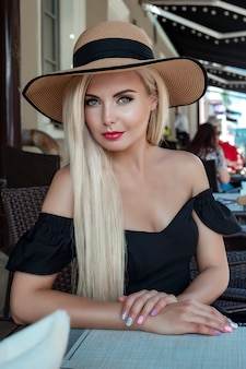 High fashion portrait of a graceful woman in an elegant straw hat and dress that sits in a cafe at a table