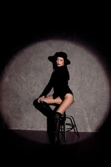 黒の帽子とボディスーツのエレガントな女性のファッション性の高い肖像画。スタジオショット。