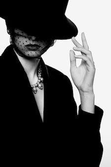 レトロな外観のエレガントな女性のファッション性の高い肖像画。黒と白の画像、黒の帽子、ジャケット、ネックレス