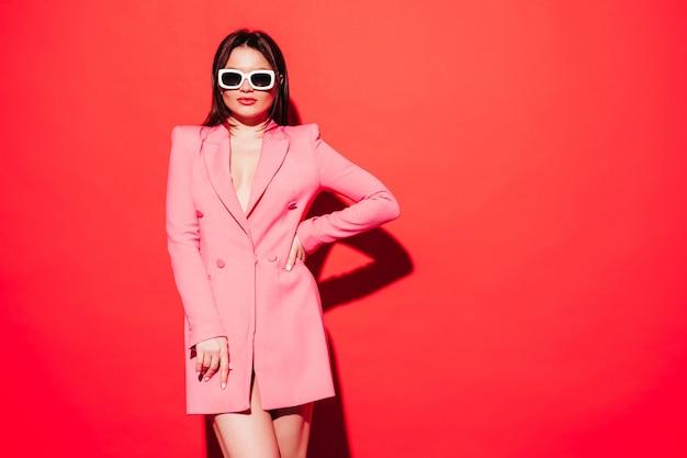 素敵なピンクの夏のスーツを着ている若い美しいブルネットの女性のハイファッションの肖像画