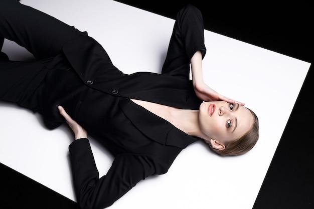 Портрет высокой моды молодой элегантной женщины в черном костюме