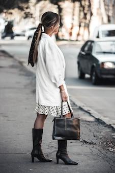 屋外のエレガントな若い女性のファッション性の高い肖像画