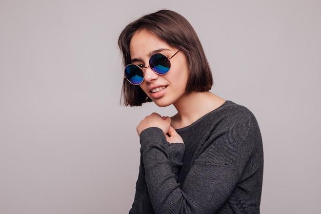 Alta moda ritratto di giovane donna elegante in occhiali da sole isolati