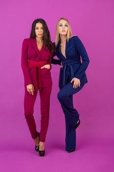 Две привлекательные женщины в стиле высокой моды на фиолетовой стене в стильных красочных вечерних костюмах фиолетового и синего цвета, друзья веселятся вместе, модная тенденция