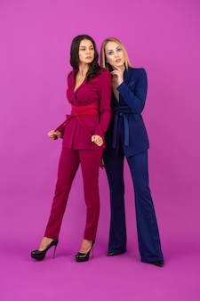 High fashion style two attractive women on violet wall in stylish colorful evening suits of purple and blue color, friends having fun together, fashion trend