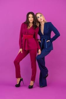 Stile di alta moda due donne attraenti sul muro viola in eleganti abiti da sera colorati di colore viola e blu, amici che si divertono insieme, tendenza della moda