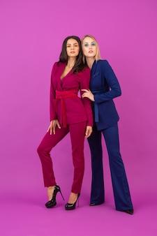 紫と青の色のスタイリッシュなカラフルなイブニングスーツ、一緒に楽しんでいる友人、ファッショントレンドの紫色の壁に2人の笑顔の魅力的な女性のハイファッションスタイル