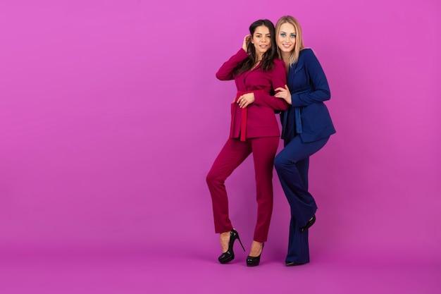 Две улыбающиеся привлекательные женщины в стиле высокой моды на фиолетовой стене в стильных красочных вечерних костюмах фиолетового и синего цвета, друзья веселятся вместе, модная тенденция