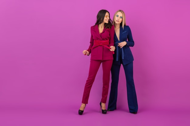 보라색과 파란색의 세련된 화려한 저녁 정장에 보라색 벽에 하이 패션 스타일 두 웃는 매력적인 여성, 친구가 함께 재미, 패션 트렌드