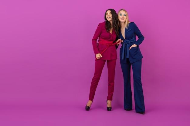 Stile di alta moda due donne attraenti sorridenti sul muro viola in eleganti abiti da sera colorati di colore viola e blu, amici che si divertono insieme, tendenza della moda