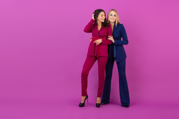 High fashion style two smiling attractive women on violet wall in stylish colorful evening suits of purple and blue color, friends having fun together, fashion trend