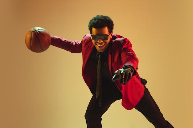 높은 패션 스타일 갈색 벽 위에 절연 농구 빨간 재킷에 남자. 뛰어난 아프리카 계 미국인 프로 스포츠맨, 운동 선수 공연, 훈련. 청소년, 자유, 광고, 판매.
