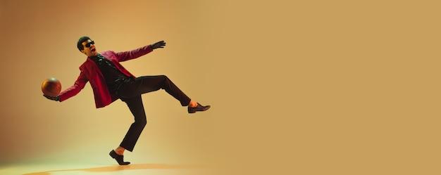 茶色の壁に隔離されたバスケットボールをする赤いジャケットを着たハイファッションスタイルの男。卓越したアフリカ系アメリカ人のプロスポーツマン、アスリートのパフォーマンス、トレーニング。若さ、自由、広告、販売。