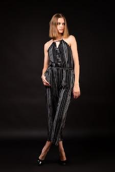 High fashion модель женщина в черном комбинезоне и кардиган на черном