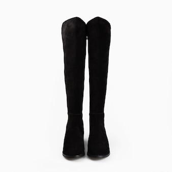 白い背景の上の高い女性の黒のブーツ