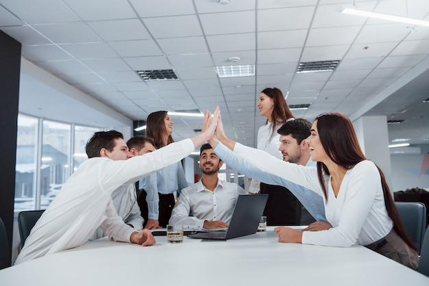 High five all. job is done. group of office workers happy to hit their own records and being successful