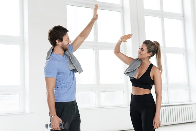 フィットネストレーニング後のジムでの男性と女性の間のハイタッチ。パーソナルトレーナーと彼のクライアントは、トレーニング中に結果を達成します。