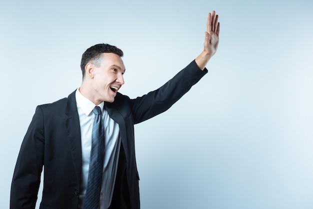 Дай пять. веселый приятный довольный мужчина держит руку и улыбается, будучи готовым дать пять