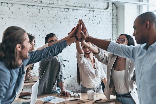 成功のためのハイタッチ!役員室で働いている間、団結と笑顔のシンボルでお互いにハイタッチを与えるビジネス同僚の多様なグループ