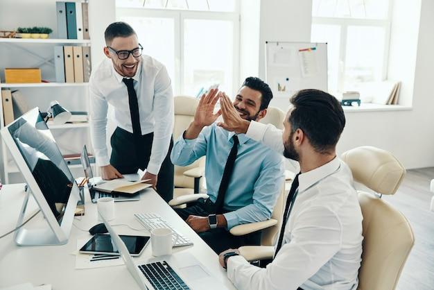 成功のためのハイタッチ。オフィスで働いている間笑顔の正装の若い現代男性のグループ