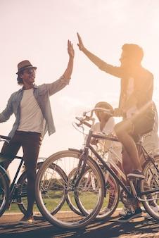 友達にハイタッチ。 2人の男性がお互いにハイタッチをしている間、道路上の自転車の近くに立っている陽気な若者のローアングルビュー