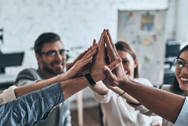 ハイタッチ!役員室で働いている間、団結と笑顔のシンボルでお互いにハイタッチを与えるビジネス同僚の上面図
