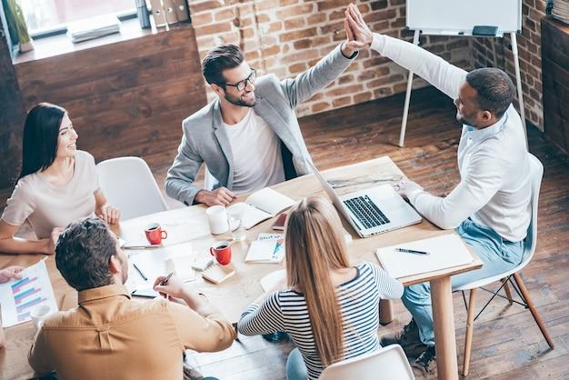 ハイタッチ!彼らの同僚がオフィスのテーブルに座っている間にハイタッチをしている2人の若い陽気な男性の上面図