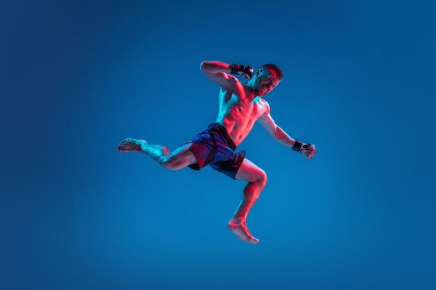 Профессиональный истребитель мма высокого полета, пробивая или бокс, изолированные на синем фоне студии