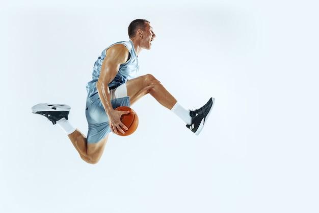 Высокий полет. молодой кавказский баскетболист команды в действии, движение в прыжке, изолированные на белом фоне. понятие спорта, движения, энергии и динамичного, здорового образа жизни. обучение, практика.