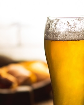High glass of beer with foam