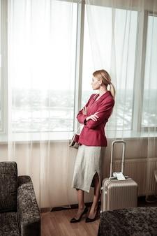 ハイヒール。ホテルの窓の近くに立っているかかとの高い靴を履いているブロンドの髪の実業家