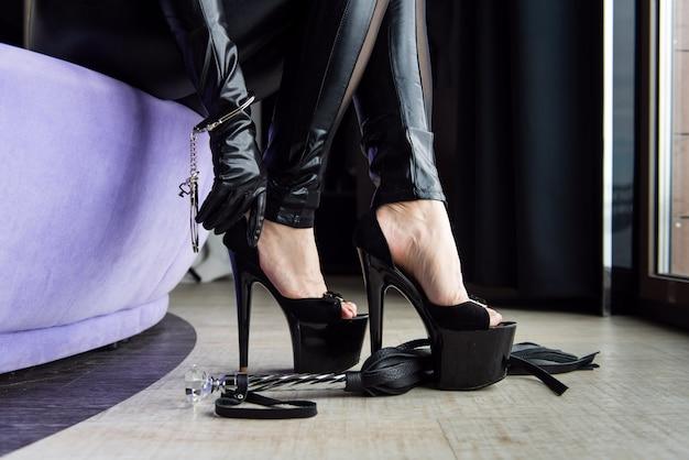 High heels, handcuffs and crop whip close-up