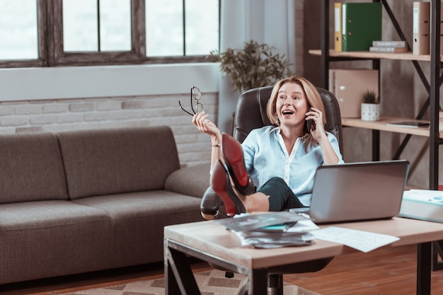 ハイヒール。電話で話すハイヒールを着てテーブルに足を置くスタイリッシュな成熟した女性