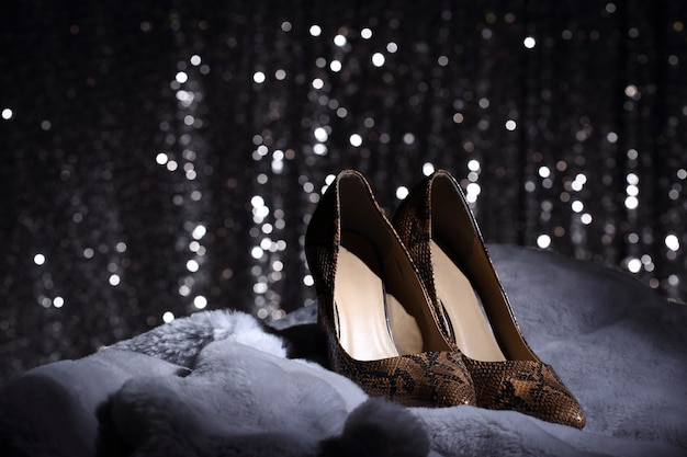 High heels shoes on fur and silver wallpaper