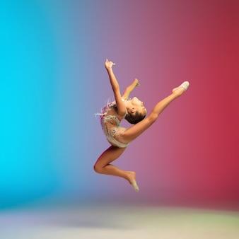 Высокий прыжок. маленькая кавказская девочка, тренировка гимнастки, выступающая изолированно на градиентном сине-красном студийном фоне в неоне. грациозный и покладистый, крепкий ребенок. понятие спорта, движения, действия.