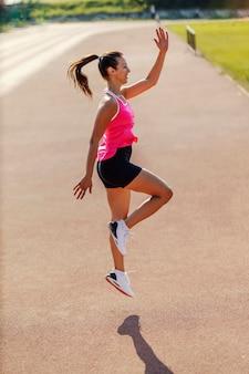 陸上競技場でのハイジャンプ。スポーティーな黒とピンクの服と白いスニーカーを身に着けたハンサムな女性が力強い動きで飛び上がります。晴れた夏の日に外で競争する準備をしている
