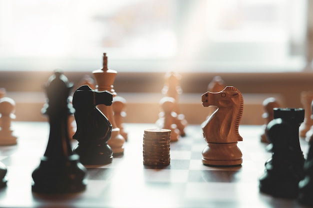 Яркий свет двух шахматных лошадей, стоящих лицом друг к другу, со стеком новых британских монет весом в один фунт в центре настольной игры.
